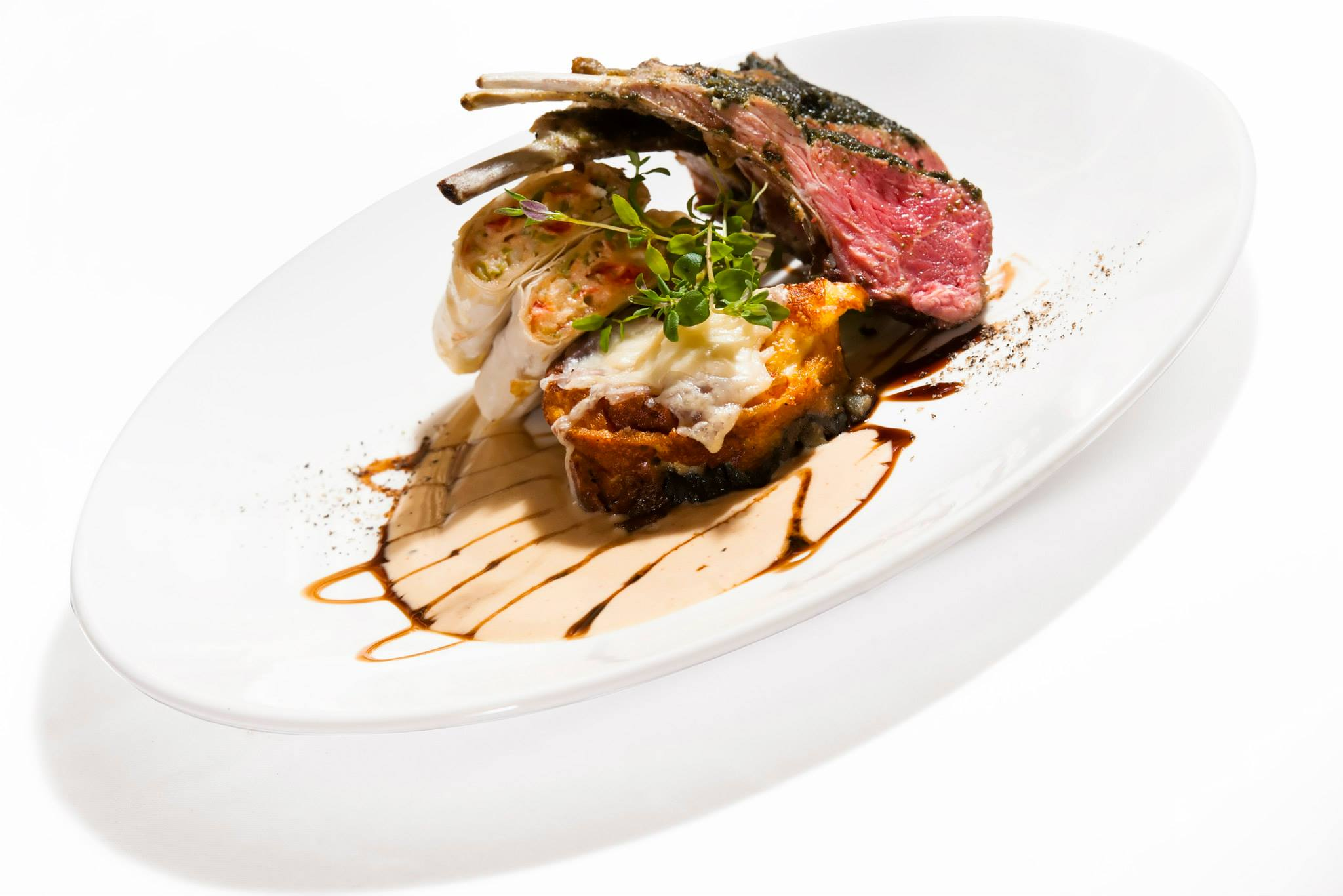 Roast lamb cutlets with mint pesto, vegetable lasagna with goat cheese strudel and calvados sauce